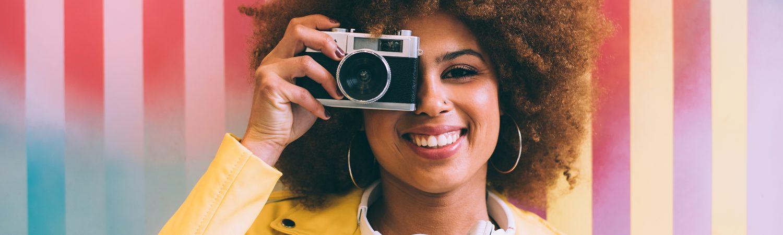 Vrouw met camera werkt aan visuele merkidentiteit